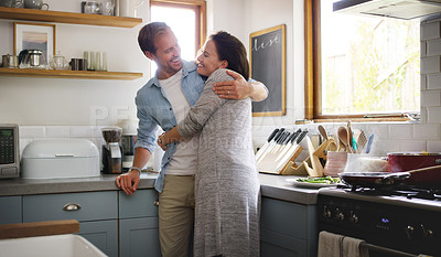 Buy stock photo Cropped shot of an affectionate young couple embracing each other while standing in their kitchen at home