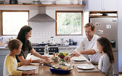 Buy stock photo Cropped shot of two affectionate young parents having a meal with their kids in the kitchen at home