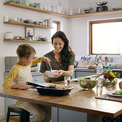 Buy stock photo Cropped shot of an affectionate young mother serving her son during a meal on their kitchen table