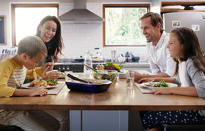 Buy stock photo Cropped shot of two affectionate young parents enjoying a meal with their kids at home