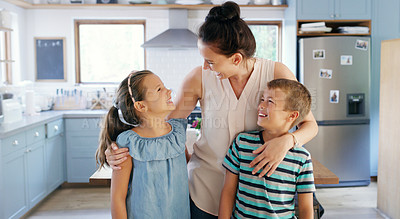 Buy stock photo Cropped shot of an affectionate young mother spending time with her two kids in their kitchen at home