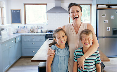 Buy stock photo Cropped portrait of an affectionate young mother looking ecstatic while holding her two kids in their kitchen at home