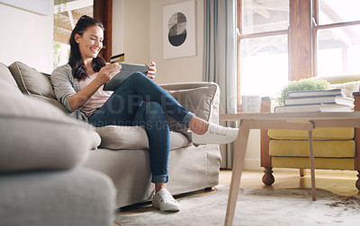 Buy stock photo Full length shot of an attractive young woman looking cheerful while shopping online using a digital tablet at home