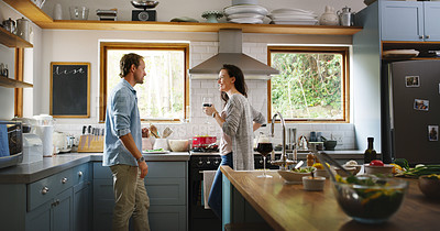 Buy stock photo Cropped shot of an affectionate young couple having a discussion while cooking in their kitchen at home