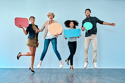 Buy stock photo Full length shot of a diverse group of businesspeople holding up speech bubbles against a blue background
