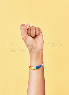 Buy stock photo Studio shot of an unrecognizable woman raising a fist while wearing a rainbow bracelet
