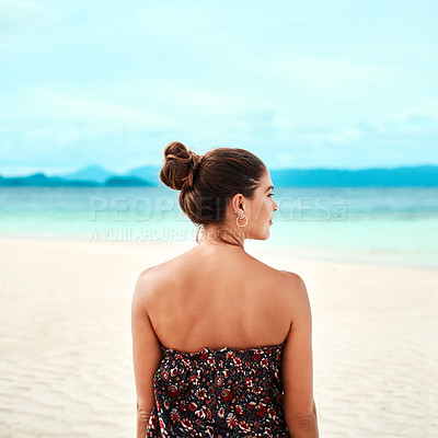 Buy stock photo Rearview shot of a young woman spending the day at the beach