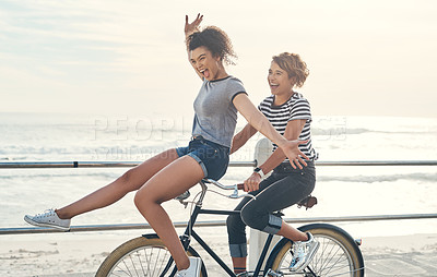 Buy stock photo Shot of two friends having fun cycling along the coastline