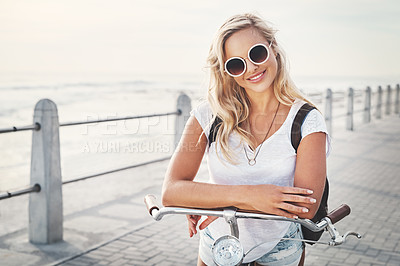 Buy stock photo Shot of a beautiful young woman out on the promenade with her bicycle