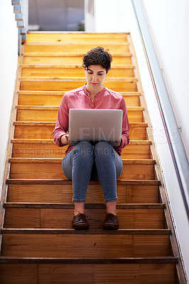 Buy stock photo Full length shot of an attractive young businesswoman sitting alone on a staircase and using her laptop in the office