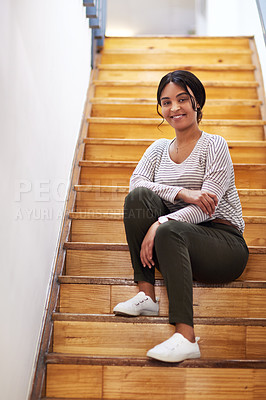 Buy stock photo Full length portrait of an attractive young businesswoman sitting alone on a wooden staircase in her office