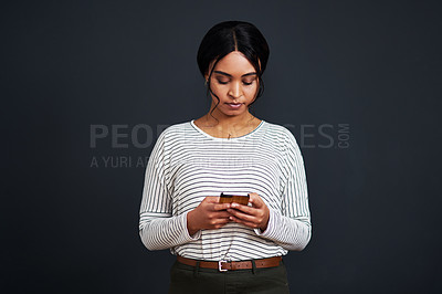 Buy stock photo Cropped shot of an attractive young businesswoman standing alone and texting on her cellphone against a black studio background