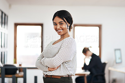 Buy stock photo Cropped portrait of an attractive young businesswoman standing with her arms folded while her colleague works behind her