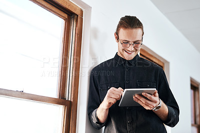 Buy stock photo Cropped shot of a handsome young businessman standing and using a tablet in his office alone