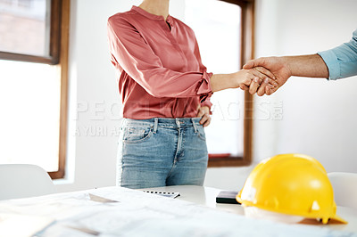 Buy stock photo Cropped shot of two unrecognizable businesspeople shaking hands in agreement over building plans in the office
