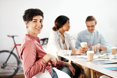 Buy stock photo Cropped portrait of an attractive young businesswoman sitting and smiling while her colleagues have a meeting behind her