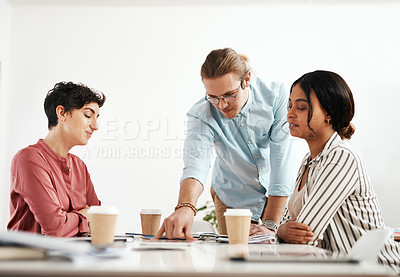 Buy stock photo Cropped shot of a diverse group of businesspeople sitting together and reading paperwork during a meeting in the office