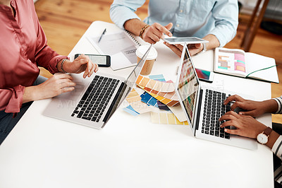 Buy stock photo Cropped shot of an unrecognizable group of businesspeople sitting together and using technology during a meeting in the office