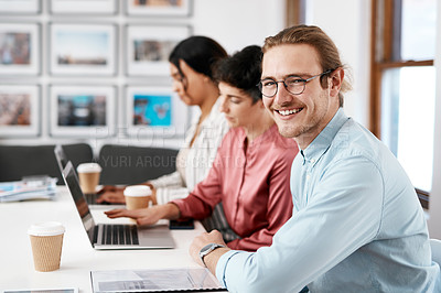Buy stock photo Cropped portrait of a handsome young businessman sitting while his colleagues work behind him in the office
