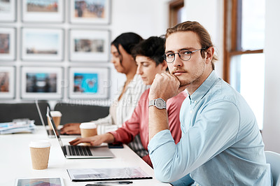 Buy stock photo Cropped portrait of a handsome young businessman sitting and looking contemplative while his colleagues work behind him in the office