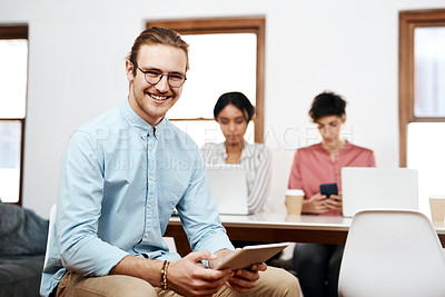 Buy stock photo Cropped portrait of a handsome young businessman sitting and using a tablet while his colleagues work behind him