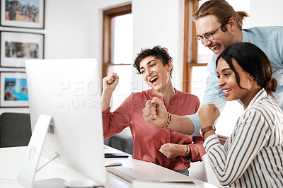 Buy stock photo Cropped shot of a diverse group of businesspeople celebrating while working on a computer together in the office