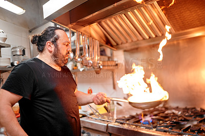 Buy stock photo Shot of a chef preparing a dish in the kitchen of a restaurant