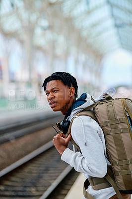 Buy stock photo Cropped shot of a handsome young man standing alone and waiting for his train at the station