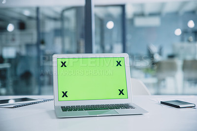 Buy stock photo Cropped shot of a green screen laptop on a desk with a tablet and cellphone in the office
