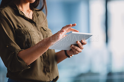 Buy stock photo Cropped shot of an unrecognizable businesswoman standing alone in her office and using a tablet