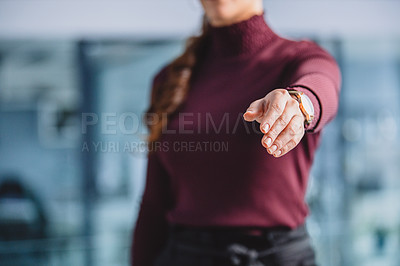 Buy stock photo Cropped shot of an unrecognizable businesswomen standing alone in her office and extending her hand out for a handshake