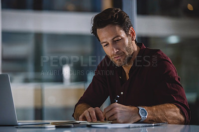 Buy stock photo Cropped shot of a handsome mature businessman sitting alone in his office and writing out notes