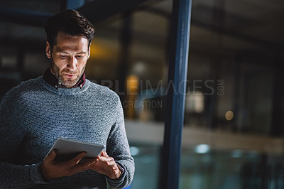 Buy stock photo Cropped shot of a handsome mature businessman standing alone in his office and using a tablet