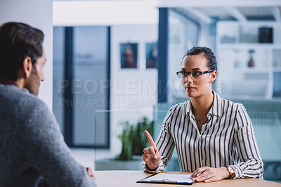 Buy stock photo Cropped shot of an attractive young businesswoman sitting with a male colleague and interviewing him in the office