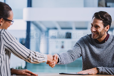 Buy stock photo Cropped shot of a handsome mature businessman shaking hands with a female colleague after a successful interview in the office
