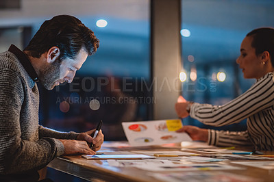 Buy stock photo Cropped shot of an attractive young businesswoman sitting and brainstorming with her male colleague in his office at night