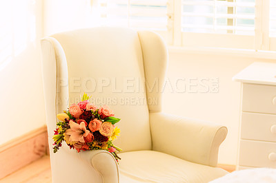 Buy stock photo Shot of flowers on a chair before a wedding ceremony
