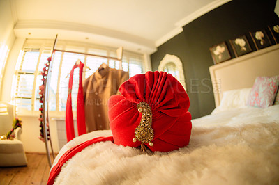 Buy stock photo Shot of a red turban on a bed before a wedding ceremony