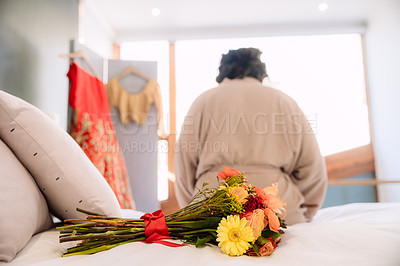 Buy stock photo Shot of a bunch of flowers on the bed with a bride sitting in the background