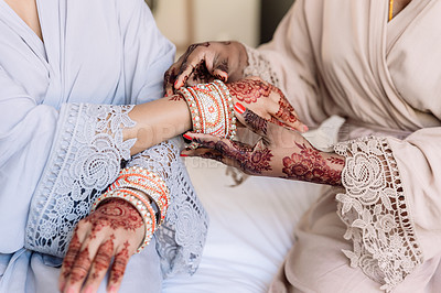 Buy stock photo Cropped shot of an unrecognizable woman getting her bracelets put on by her bridesmaid on her wedding day