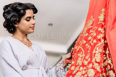 Buy stock photo Shot of a beautiful young woman feeling the fabric of her dress on her wedding day