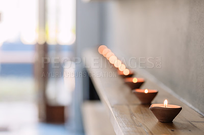 Buy stock photo Shot of lit candles in a row in an empty home