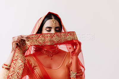 Buy stock photo Studio shot of a beautiful young woman covering her face with her veil on her wedding day