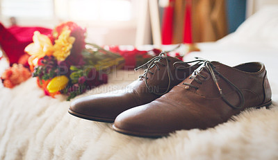 Buy stock photo Shot of men's shoes and a bunch of flowers on a bed before a wedding ceremony