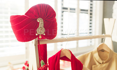 Buy stock photo Shot of a turban and men's clothing hanging on a rack in a bedroom before a wedding ceremony