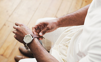 Buy stock photo Shot of an unrecognizable man putting on a watch in preparation for his wedding