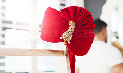 Buy stock photo Shot of a turban on a clothing rack with a man getting ready for his wedding day in the background