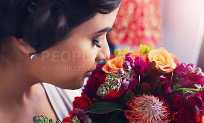 Buy stock photo Shot of a beautiful young woman smelling a bunch of flowers before her wedding