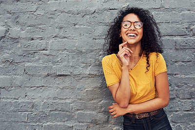 Buy stock photo Cropped shot of an attractive young woman wearing spectacles and smiling while standing against a gray background outdoors
