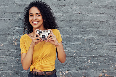 Buy stock photo Cropped portrait of an attractive young woman holding a camera and standing alone against a gray background